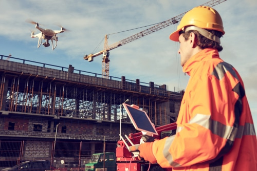 man flying a drone in a building development wearing secure wear